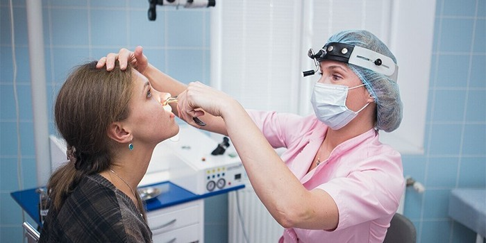Врач обследует нос пациентки