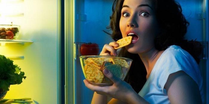 Девушка ест крекер перед открытым холодильником